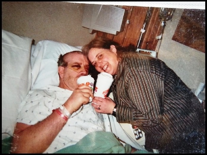 Paul in his hospital bed having a cup of coffee with his wife