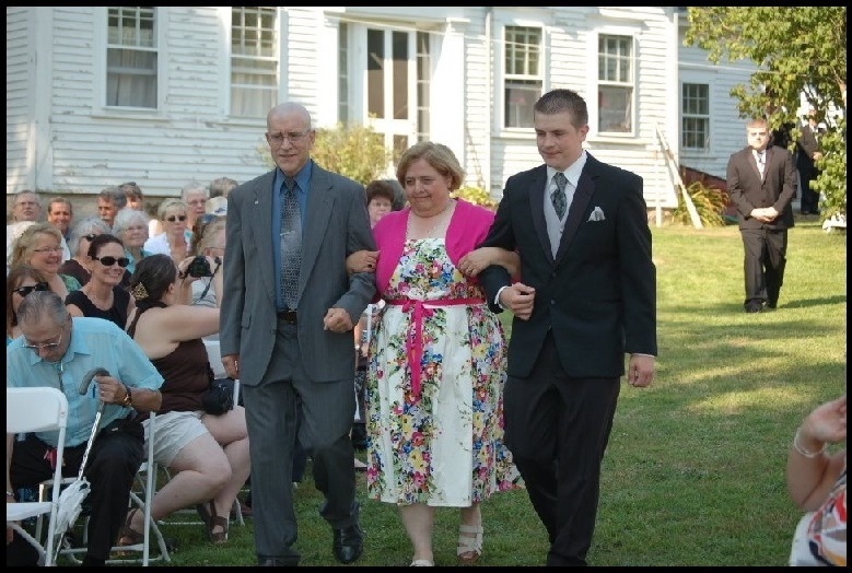 Paul arm in arm with his wife and son at his son's wedding