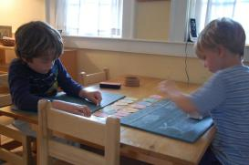 two male elementary students working on a chalkboard writing exercise