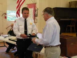 Westport Volunteer Fire Department Deputy Fire Chief Jason Abbott accepts state flag from State Sen. Chris Johnson